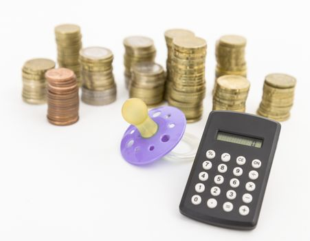 pacifier with hard money and small pocket calculator in light background.