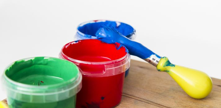 paint in small tubs with paint brush on wooden table