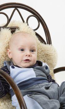 newborn child in rocking chair. studio shot