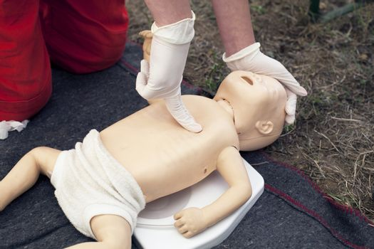 Paramedic demonstrates CPR on infant dummy