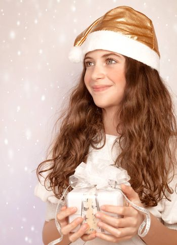 Closeup portrait of beautiful Santa girl holding in hands cute white gift box, wintertime holidays, Christmas joy, happiness concept