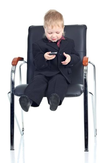 Little businessman with a phone on a chair