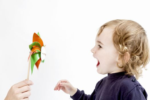 cute girl blowing to colorful windmill. studio shot in light grey background