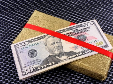 Holiday bonus. Money on red bow decorated gift box