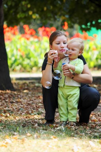 Young woman with her son blows bubbles in a city park