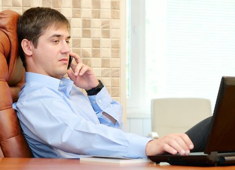 Man in the office talking by phone and loking into laptop