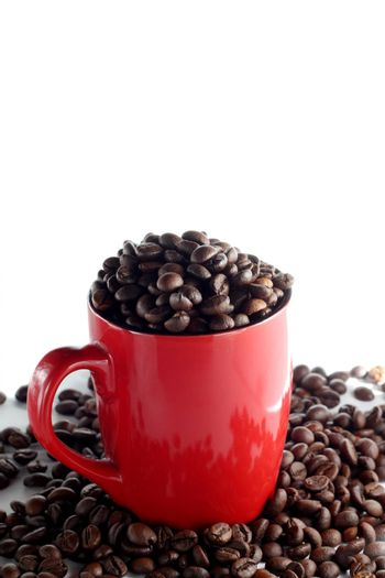 Red cup full of roasted brown coffee beans