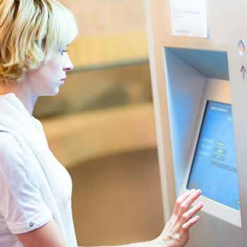 Lady using ticket vending machine.
