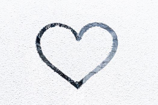 Heart drawn on frosty window.