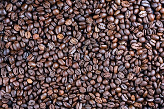 Many roasted coffee beans at background