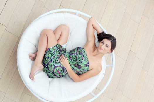 Young woman lies in the circle deck chair