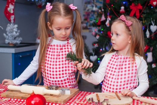 Little charming sisters bake gingerbread cookies for Christmas