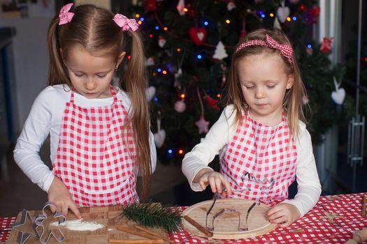 Little cute sisters bake gingerbread cookies for Christmas