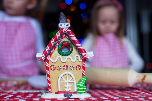 Gingerbread fairy house decorated by colorful candies on a background of little girls