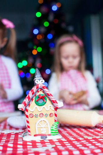 Gingerbread fairy house decorated by colorful candies on a background of little girl