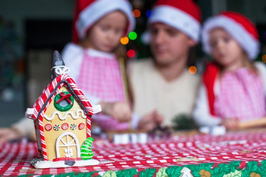 Gingerbread fairy house decorated by colorful candies on a background of happy family