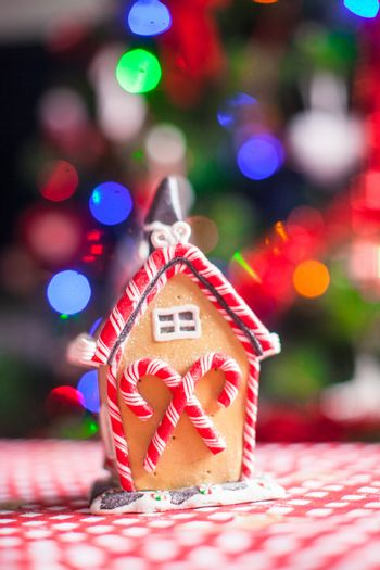 Gingerbread house decorated by colorful candies on a background of bright Christmas tree with garland