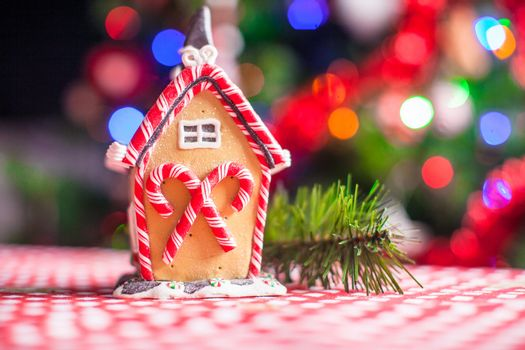 Close-up Gingerbread fairy house decorated by colorful candies on a background of bright Christmas tree with garland