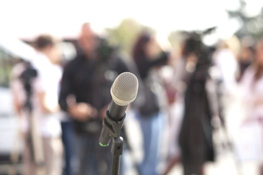Microphone in focus against blurred audience
