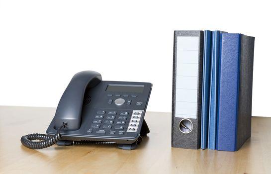 modern business phone with ring binder an folder on wooden desk
