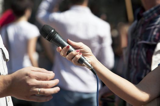 A journalist is making a interview with a microphone