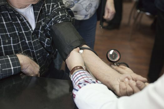 Doctor/nurse checking senior men blood pressure