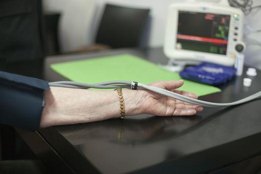Doctor/nurse checking senior woman blood pressure