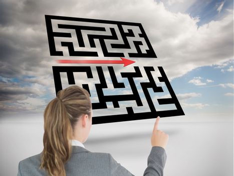 Businesswoman pointing at holographic maze