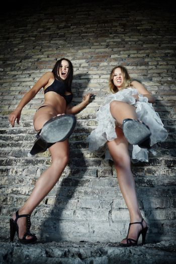 Two angry women kicking to the camera