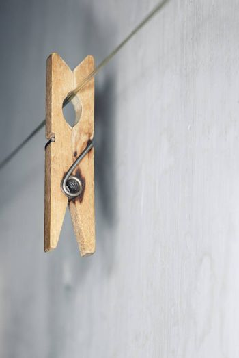 Close-up vertical photo of the old wooden clothes pin hanged on a clothes-line