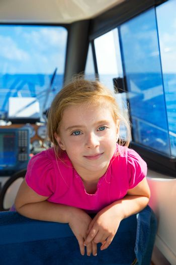 Blond kid girl at boat indoor sailing smiling happy looking camera