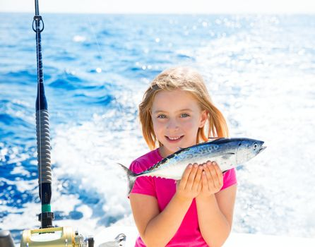 Blond kid girl fishing tuna little tunny happy with trolling catch on boat deck