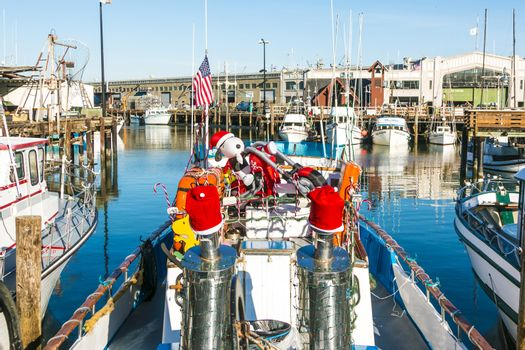 SAN FRANCISCO - DEC 9: sailing boats at Fishermans Wharf on December 9, 2013 in San Francisco, USA.  Sailing boat is decorated with Snoopy and Santa Claus heats.