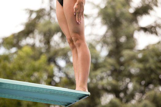 Girl standing on springboard, preparing to dive