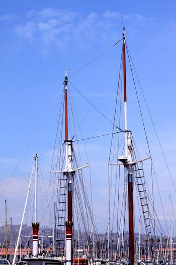 rigging of a sail boat with the blue sky in the background