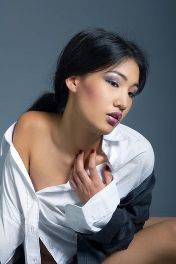 Vertical photo of the beautiful Asian lady in the shirt with naked shoulder