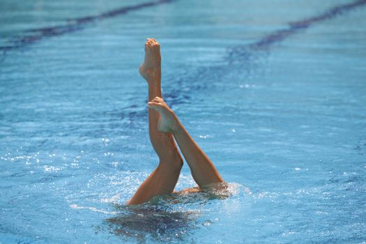 Synchronized swimmers legs point up out of the water in action