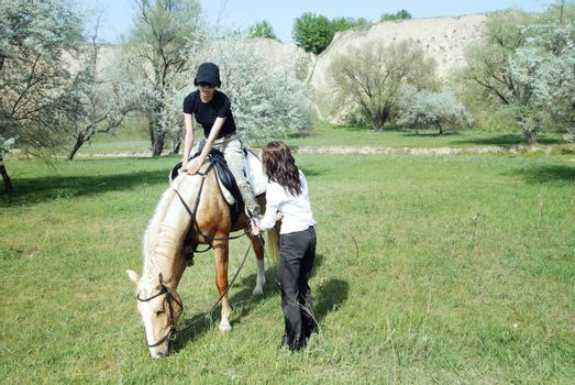 Lady riding on the horse with her trainer outdoors. Natural light and colors