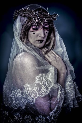 Salvation, aith concept, woman dressed in white veil and crown of thorns, virgin