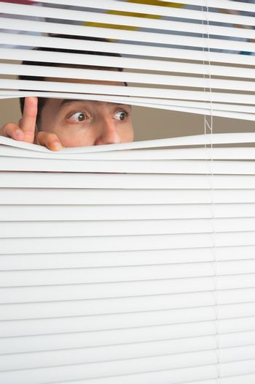 Male eyes spying through roller blind