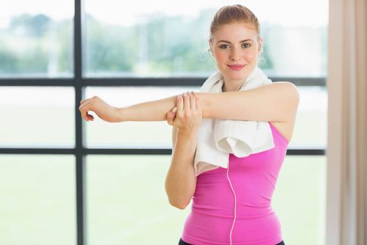 Portrait of a fit woman with towel around neck stretching hand in fitness studio