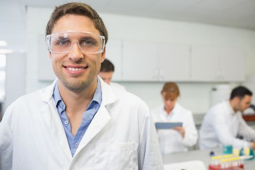 Portrait of a smiling scientist with colleagues at work in the laboratory