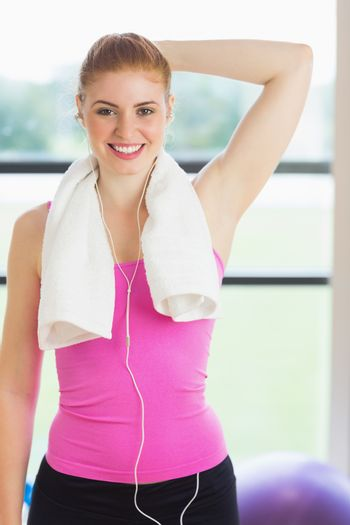 Portrait of a fit woman with towel around neck at fitness studio