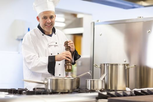 Smiling head chef flavoring food with pepper