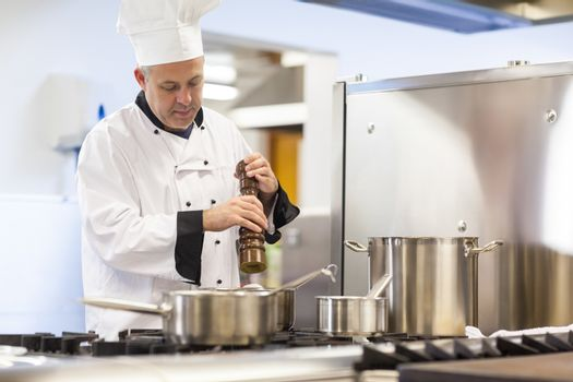 Focused head chef flavoring food with pepper