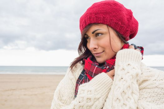 Woman in knitted hat and pullover on the beach