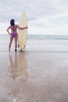 Slender woman in bikini with surfboard on beach