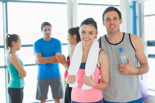 Portrait of a fit couple with friends standing in background in bright exercise room