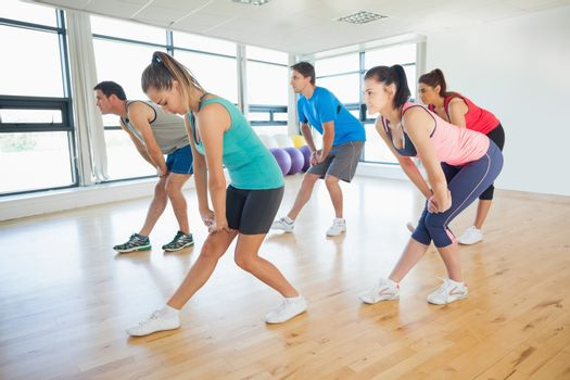 Full length of fitness class and instructor doing power fitness exercise in fitness studio