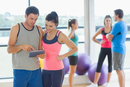 Fit couple looking at digital table with friends chatting in background in bright exercise room